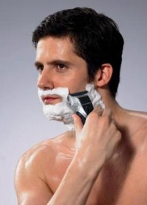 guy using electric razor with shaving cream